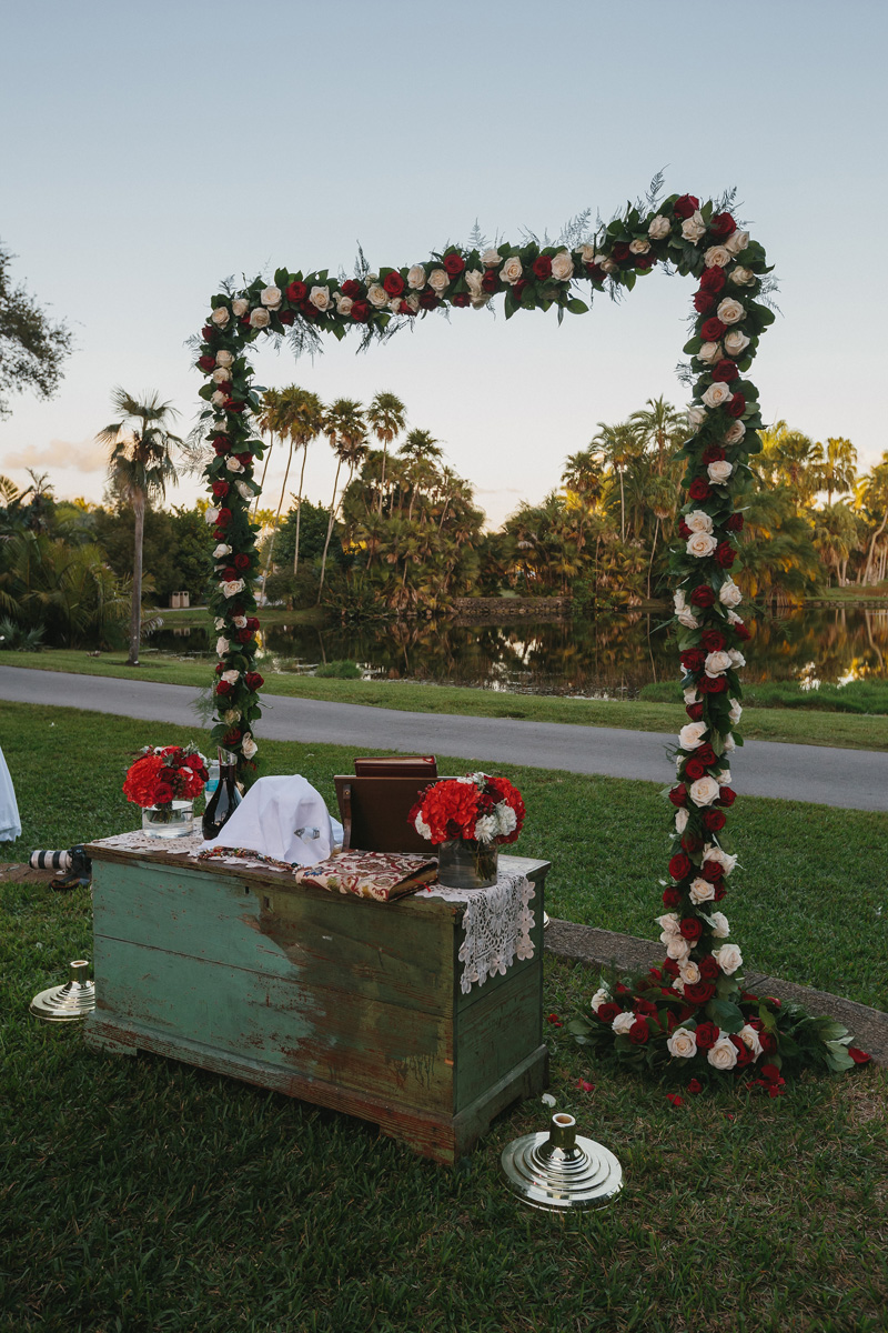 Elegant Wedding Arch in the Bailey Palm Glade with Red and White Roses | The Majestic Vision Wedding Planning | Fairchild Tropical Garden in Coral Gables, FL | www.themajesticvision.com | Robert Madrid Photography
